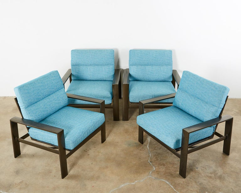 Luxurious set of four John Caldwell for Brown Jordan Parkway collection patio and garden lounge chairs. Constructed from aluminum with a rich, bronzed finish. The chairs feature a generous frame with a