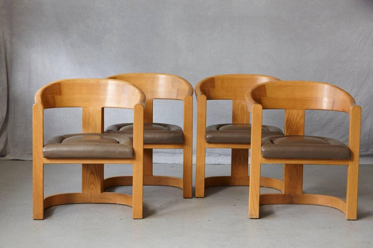 Set of four 'Onassis' chairs in oak and grayish brown leather with white baseball stitching, designed by Karl Springer in the 1980s. The leather has some age appropriate light scratches, otherwise in a very good condition.
