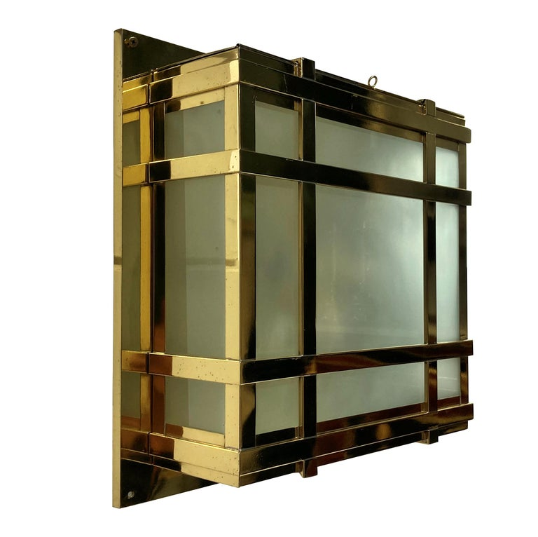 A set of four large American Modernist wall lights in lacquered brass, with opaque glass panels. Each with a door and provision for four lights inside each.