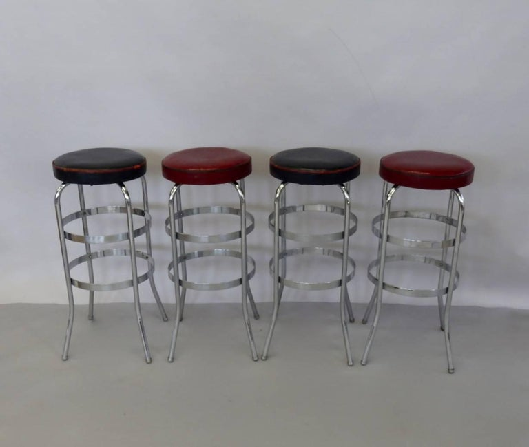 Four Lloyd chrome bar stools attributed to KEM Weber. Tubular steel legs connected with flat