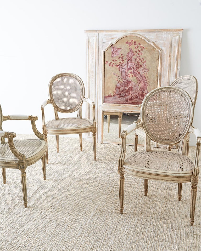Elegant set of four French Louis XVI style dining chairs of armchairs. Featuring a hand caned seat and back with a lacquered frame in the Gustavian taste. Beautifully carved with round backs and molded arms attached to a bow front seat with