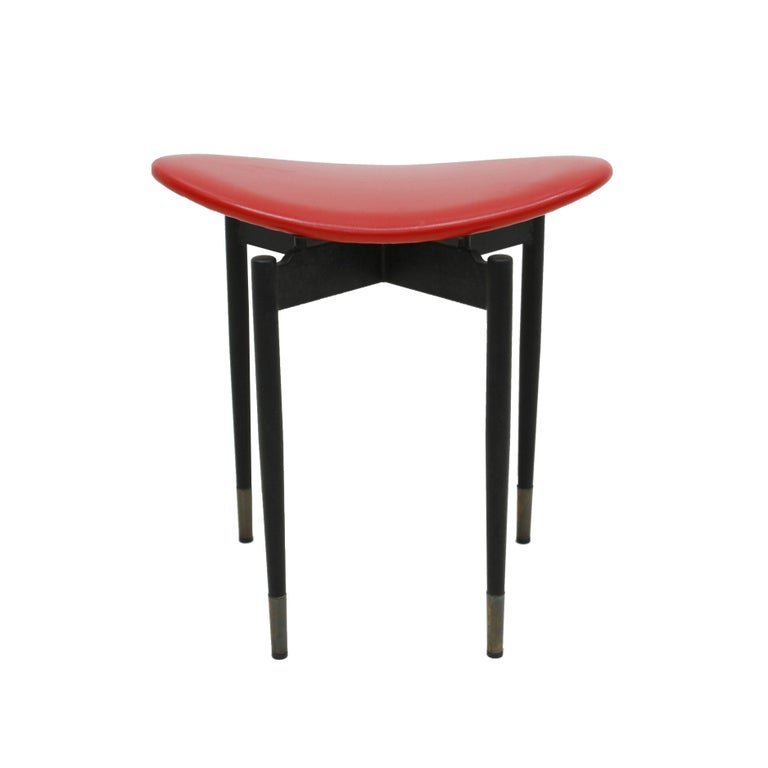"Set of four stools ""Lutrario"" designed by Carlo Mollino. Made in black enameled steel, with brass finishes and curved seat upholstered in red vinyl leather, Italy, 1959."