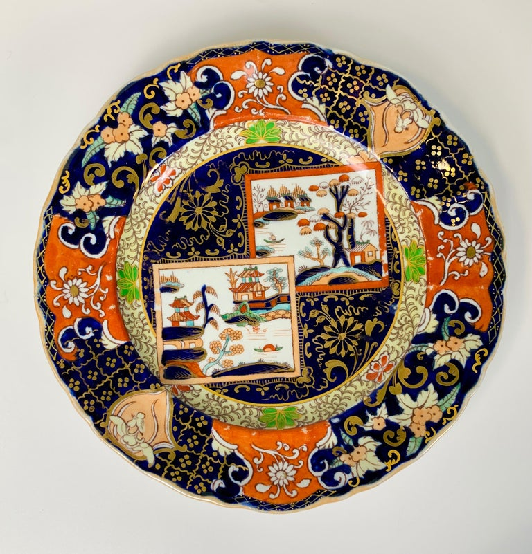A set of four Mason's ironstone plates made in England 1834-1842. The colors are vibrant; deep cobalt blue and bright orange. They are beautifully decorated with floral designs of peach-colored and white flowers and turquoise leaves. In the center
