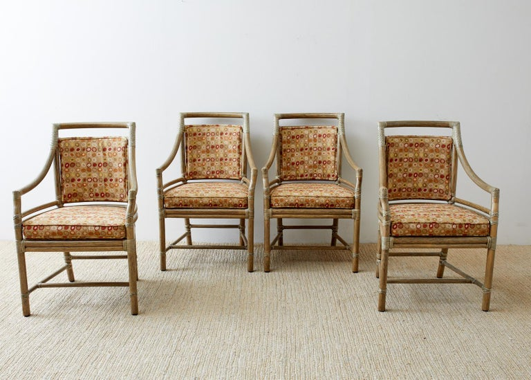 Stylish set of four genuine McGuire bamboo rattan target dining chairs or armchairs designed by Elinor McGuire. The frames feature the famous target motif on the back splat and are finished in bespoke mushroom shade. Upholstered with a midcentury
