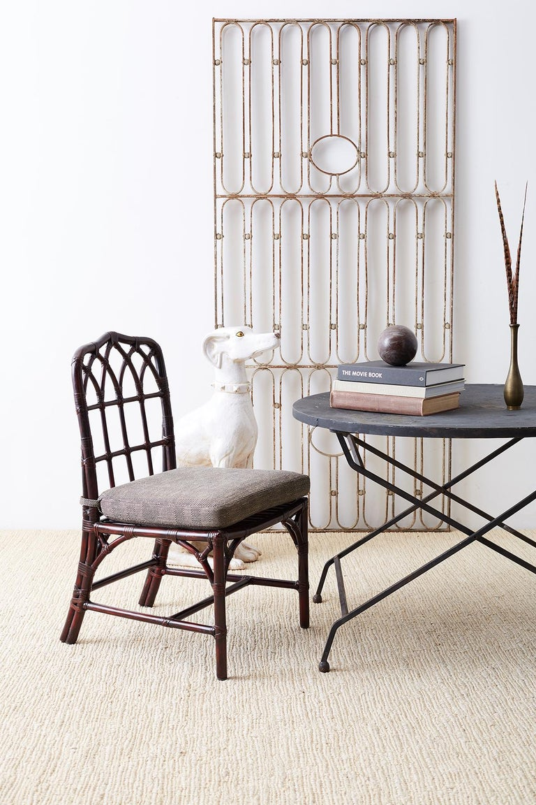 Stylish set of four McGuire bamboo rattan dining chairs featuring a rare option lacquered finish. Authentic cathedral style bamboo frames with makers labels. Professionally lacquered by Mcguire in a dark garnet color. The frames are reinforced with
