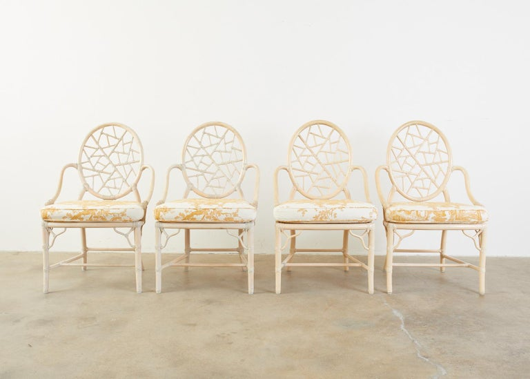 Fantastic set of four genuine McGuire bamboo rattan dining chairs. The chairs feature an iconic design by Elinor McGuire of a cracked ice open fretwork back. Handcrafted from pieces of rattan joined by leather rawhide laces. The chairs have a caned