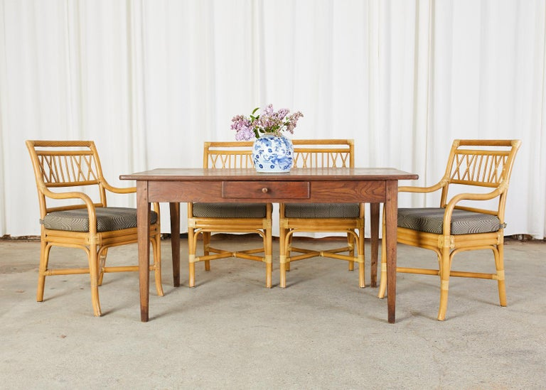 Impressive set of four bamboo rattan dining armchairs made in the manner and style of McGuire. The chairs have a square back with a faux rope twist top rail. The arms gracefully curve down to the generous seat topped with a loose seat cushion. The
