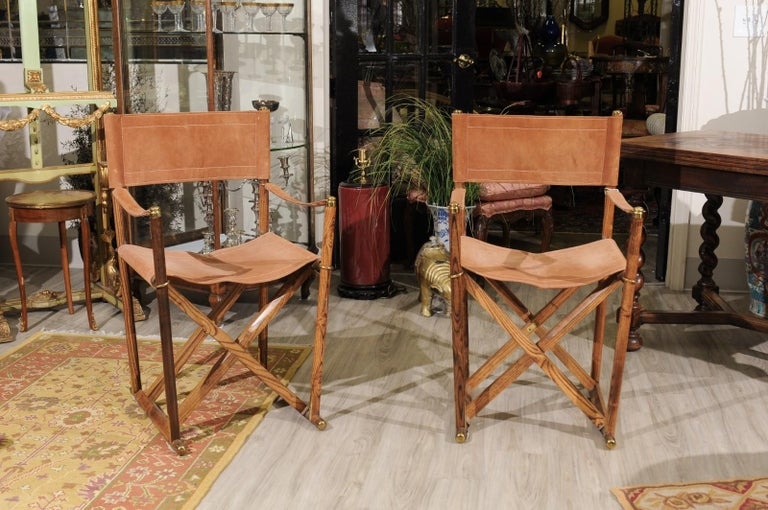 The set of campaign / director armchairs are made by Valenti, a company which started in Barcelona in 1798. The frame is teak with tan suede seats and backs. Solid brass trim