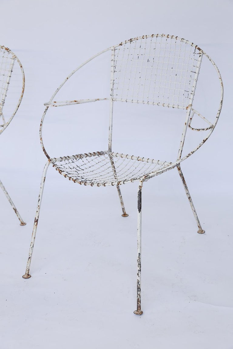 This set of four French midcentury garden or patio chairs are strong and sturdy. Each iron chair stands on four legs with a wide rounded back, and arm rests making them beautiful and comfortable. The paint is worn and rusted in some places showing