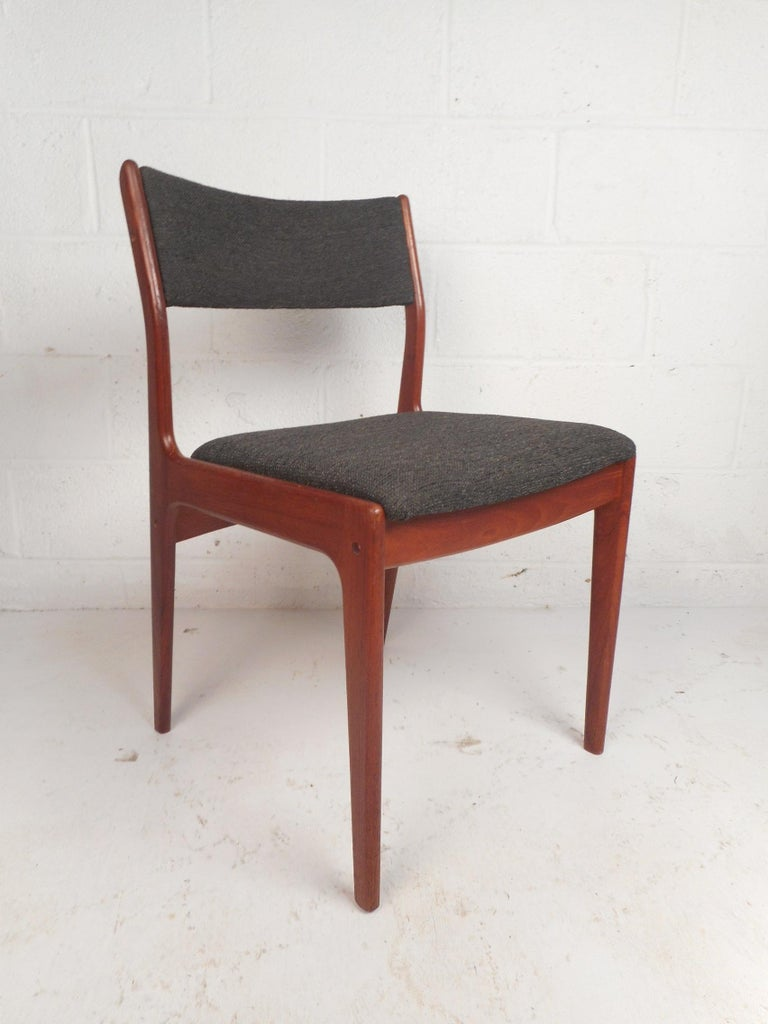 This gorgeous set of four dining chairs feature sculpted teak frames and tapered legs. Sleek design with a curved back rest ensuring maximum comfort without sacrificing style. A thick padded seat and back rest covered in a beautiful dark colored