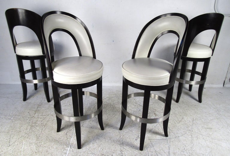 This stunning set of four vintage modern Italian barstools feature a two-tone black and white design. The overstuffed seats and backrests are covered in white vinyl. A sturdy wood frame painted in black offers the convenient ability to swivel. A
