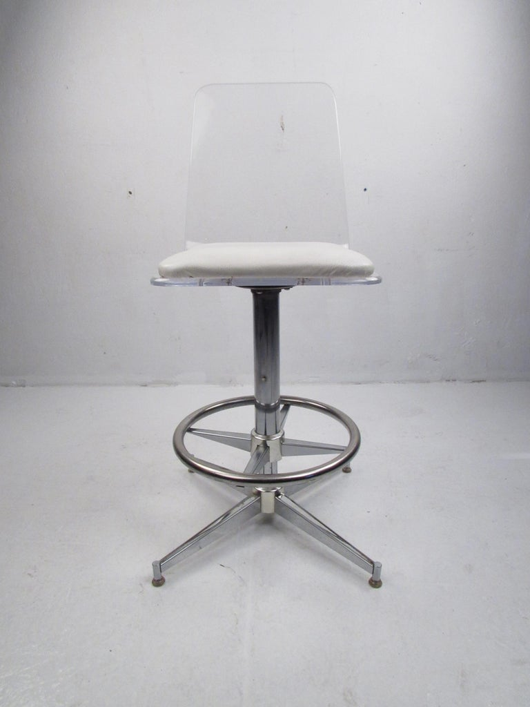 A stunning set of four vintage modern bar stools with Lucite seats and a chrome swivel base. The sleek design offers comfort with its thick cushion covered in white vinyl and a conveniently placed circular kick rest for your feet. Stylish and sturdy