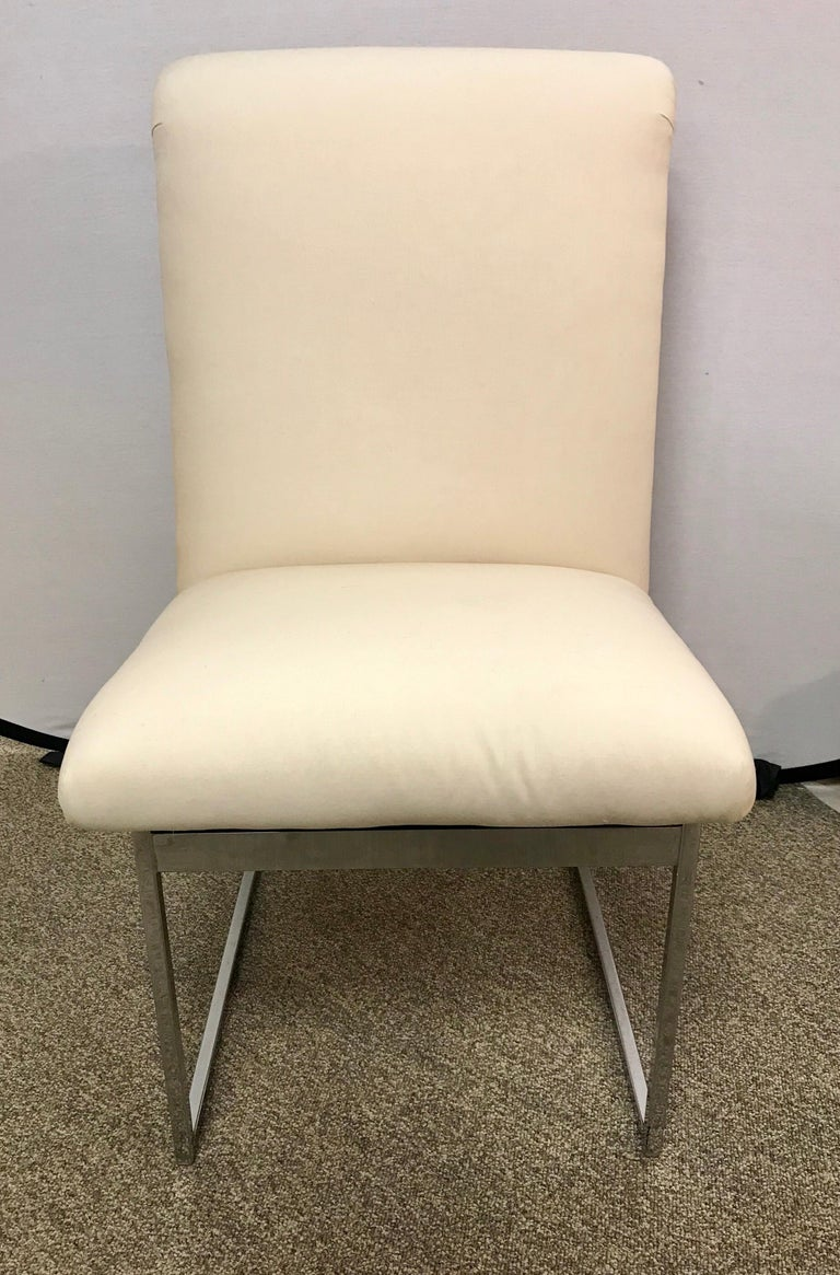 Elegant set of Milo Baughman style midcentury chairs with polished steel and off white newer fabric.
