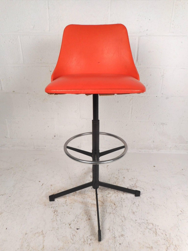 Stunning set of four vintage modern bar stools with orange vinyl covered seats and a sturdy metal base. Sleek design features a unique back rest with thick padded seats and a circular kick rest for convenience. The two-tone base and the splayed legs