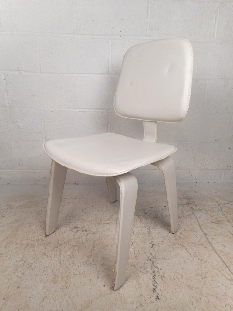 An elegant set of four vintage modern white leather side chairs with stitched leather and bent legs. This unique set offers maximum comfort without sacrificing style in any seating arrangement. A stylish design with a cushioned seat and backrest
