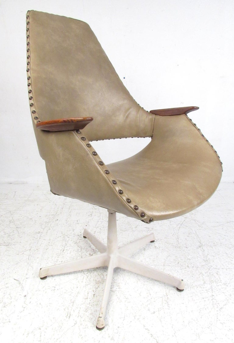 Unique set of vinyl covered swivel chairs with wood armrests and painted metal 5-point star bases. Please confirm item location (NY or NJ) with dealer.