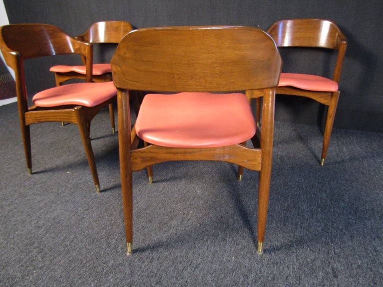 These striking Mid-Century Modern chairs combine an elegant walnut frame with salmon seats and brass footing on the chair legs. Perfect for any dining room or home setting, these chairs are full of sturdy quality and vintage style. Please confirm