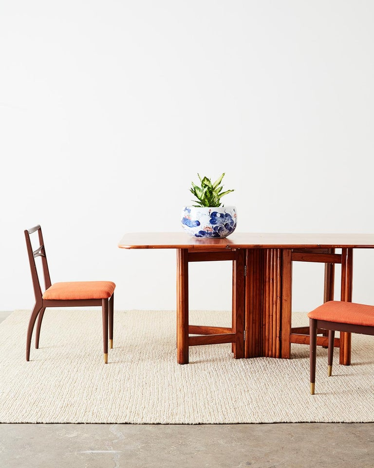 Sleek set of four Mid-Century Modern dining chairs featuring a chocolate colored lacquer finish. The painted frames have a simple elegant style with a narrow, ladder style backsplat and thin upholstered seat in a playful orange textured fabric.