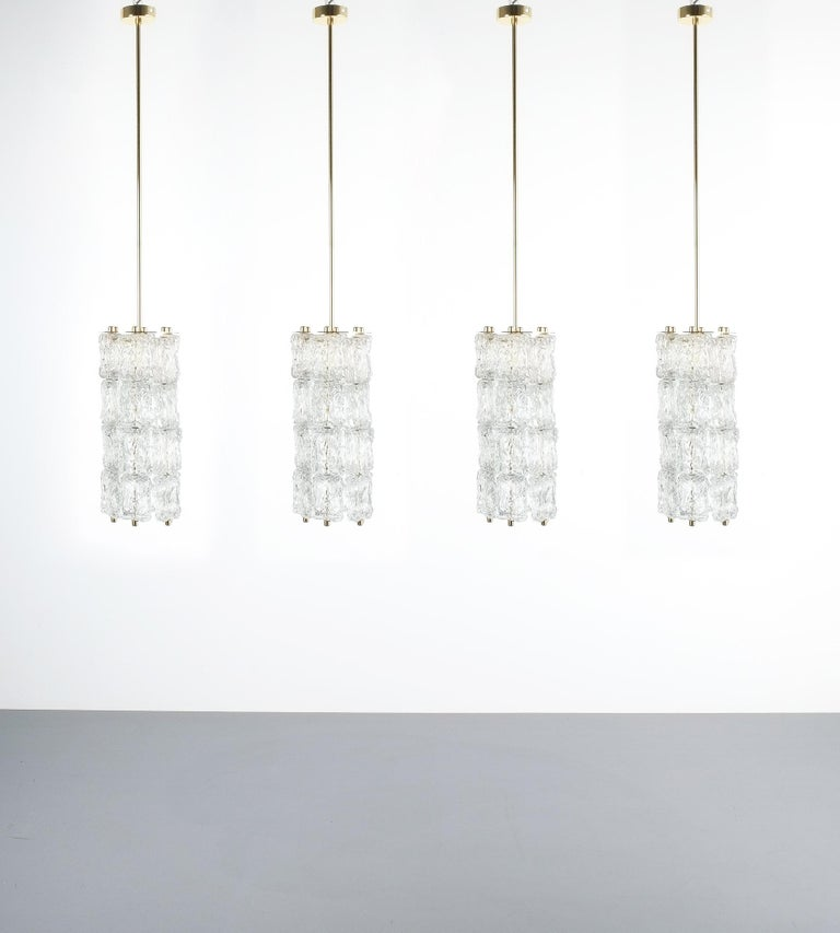 Set of four midcentury Murano glass pendant lamps by Barovier Toso, Italy.   Sold and priced per piece. Very rich and beautiful, refurbished pendant lights with clear textured glass suspending from a metal frame with gold patinated brass balls.