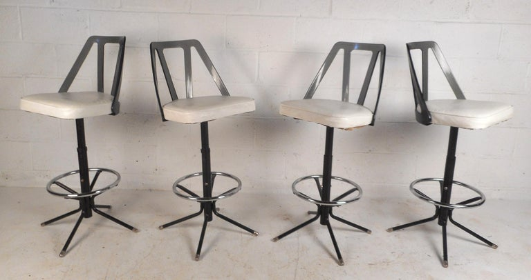 This beautiful set of four vintage modern bar stools feature unique tinted Lucite back rests and white vinyl upholstery. A comfortable design with the ability to swivel and a conveniently placed circular kick rest. A sleek design with a sturdy metal