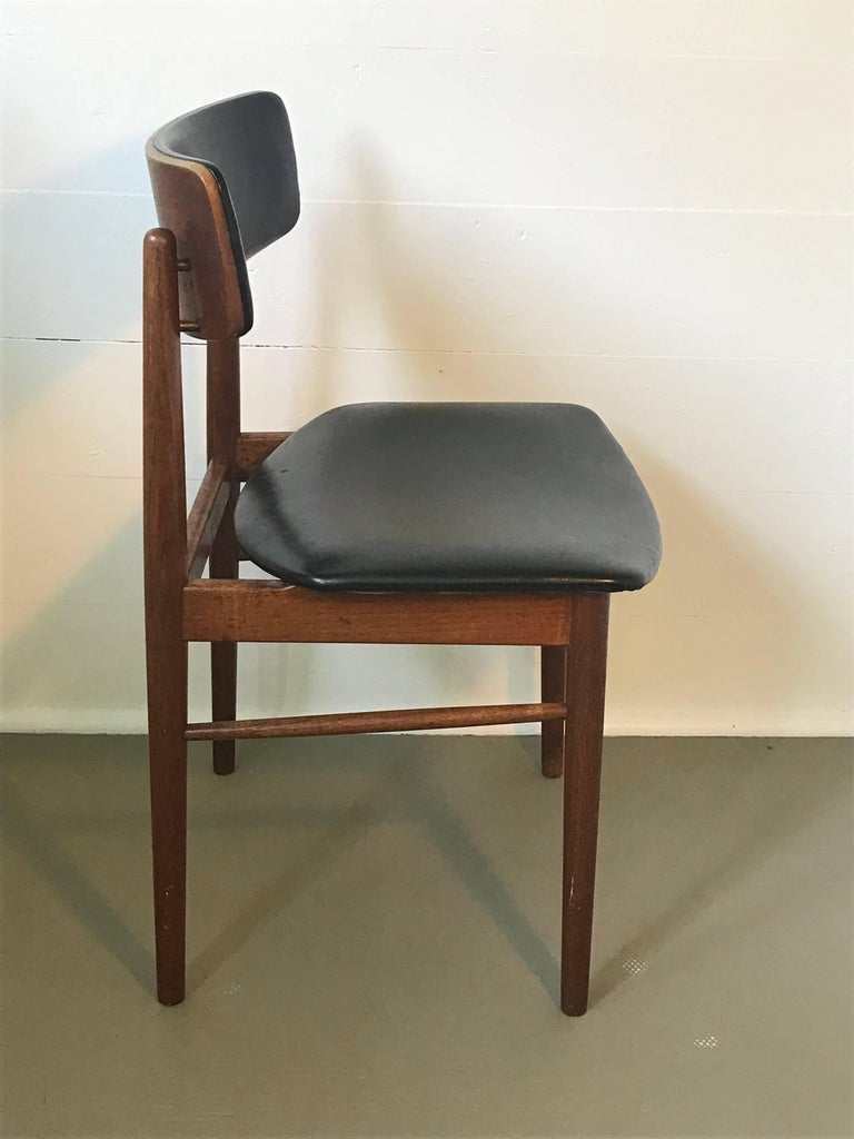 Nice set of four Mid-Century Modern teak dining chairs with original black vinyl seats and backrest, similar to the designs of Arne Vodder, Denmark. The chairs are structurally sound and in good condition for their age and use, vinyl in good