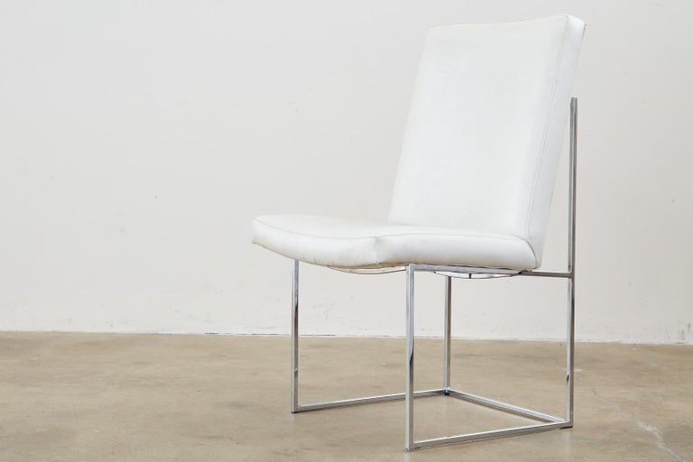 Iconic set of four thin line chrome dining chairs by Milo Baughman for Thayer Coggin. The chairs feature a chrome-plated steel frame topped with vintage faded vinyl upholstered white cushions. From an estate in Hollywood, CA. Model #1187 known as