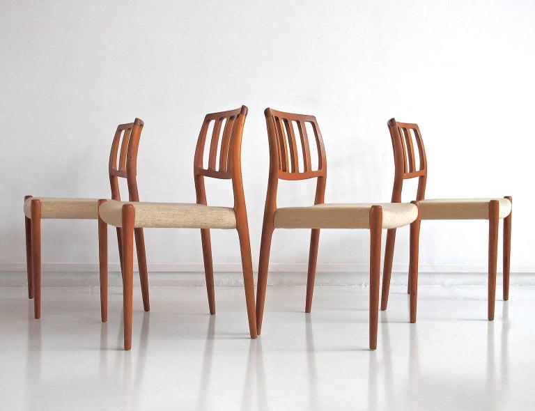 Four dining chairs, model 83, designed by Niels O. Møller in 1974. Organic design of solid wood. Seats with light beige mottled wool fabric. Manufacturer stamp underneath.