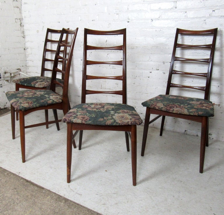 Mid-Century Modern set of four dining chairs featuring a high slatted back and floral upholstery.  (Please confirm item location - NY or NJ - with dealer).