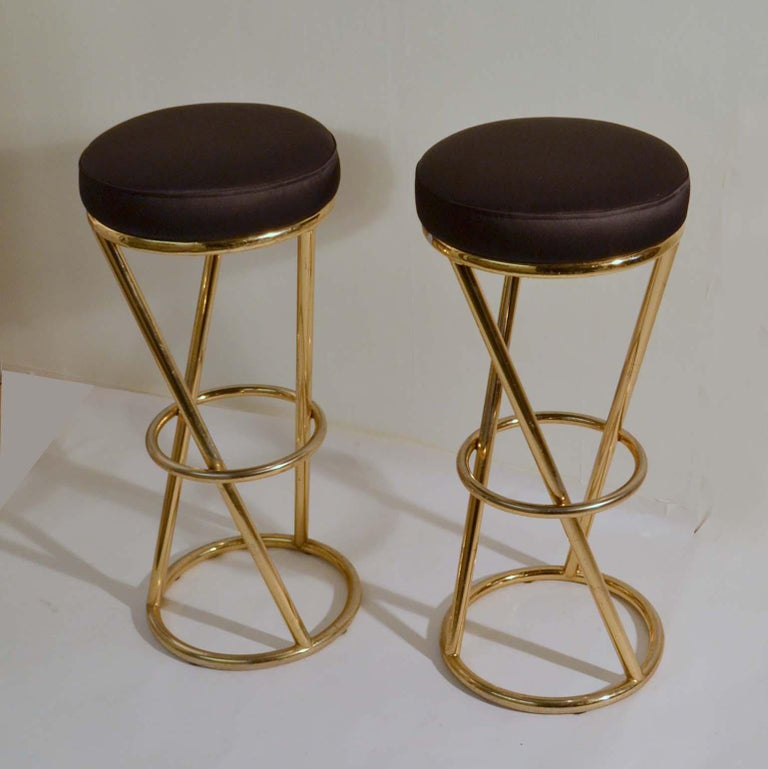 Circular bar stools have tubular brass plated metal frames. Designed by Pierre Chareau in the 1930s (Art Deco). This is a 1980s re-edition.