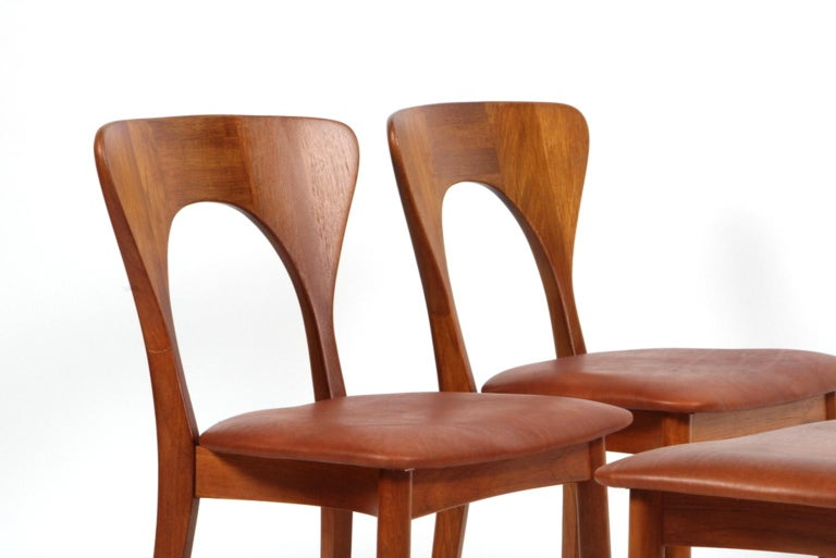 Set of four Niels Koefoed dining chairs in massive teak.  New upholstered with cognac aniline leather.  Made by Koefoeds Møbelfabrik.