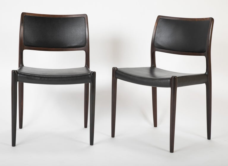 A set of four Danish Niels Moller dining chairs upholstered in black leatherette.