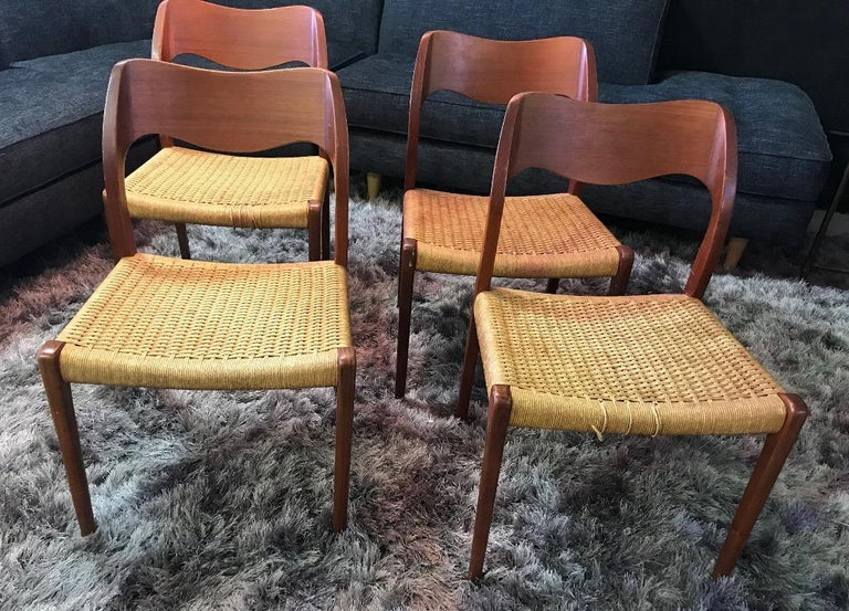 A beautiful set of four cleanly designed dining chairs by famed 20th century Danish designer Niels Otto Møller. Simple, yet elegant. Originally designed in 1951. This set still retains the original paper cord, which need some light restoration on