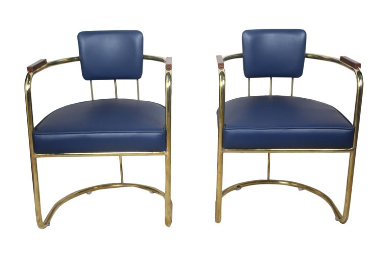 Four brass captain's chairs to use as dining chairs, card table chairs or a pair to use as occasional side chairs. Priced as a pair. Reupholstered navy blue cushions, late 1900s. Teak armrests. From the salon of a cruising ship.