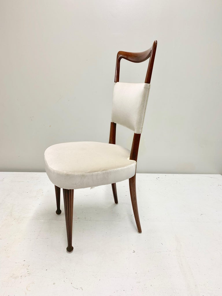 Set of four Osvaldo Borsani dining chairs with a solid and heavy rosewood structure, newly reupholstered with a light gray 100% cotton velvet from Italy. The seat cushion is comfortable and wide, the front legs are carved in the wood and adds up an