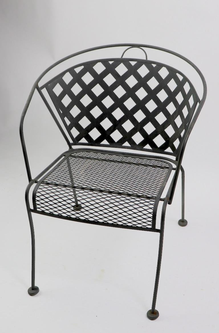 Set of four wrought iron and metal mesh dining height armchairs attributed to Woodard Furniture Company. Each chair has a wrought iron frame, metal mesh seat and larger weave pattern mesh back. All four are in very good original condition showing