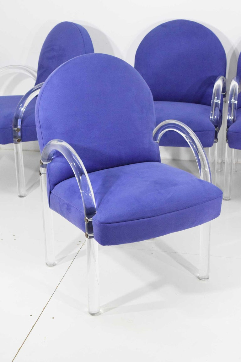 Chairs have curved Lucite arms and are upholstered in a rich lavender microfiber. Brass fittings. Upholstery is wonderful or you can change if you desire. Foam is great as well.  Sold in sets of two.