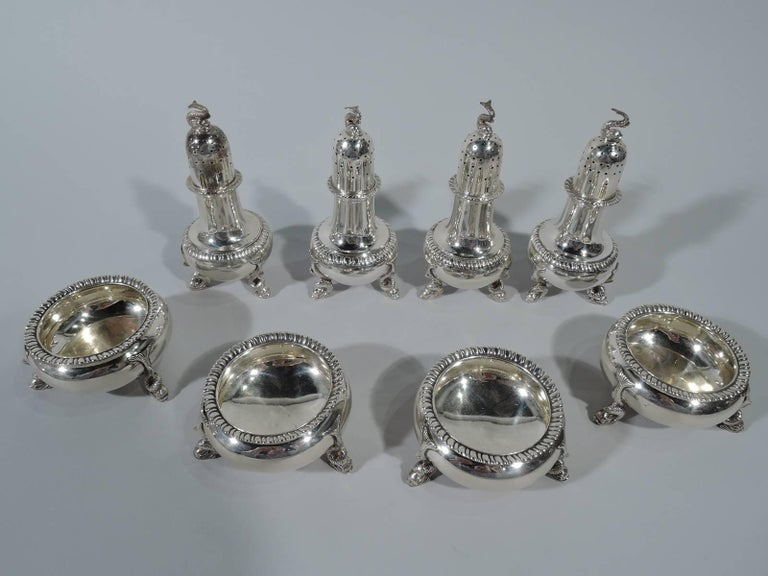 Four pairs of sterling silver open salts and pepper shakers. Made by Tuttle in Boston, 1929-1930. Each salt: Bellied bowl with gadrooned rim and three dolphin supports. Each pepper: Baluster with pierced domed cover, gadrooning, and three dolphin