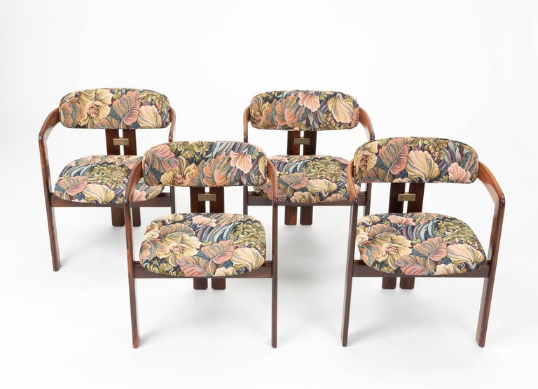 Set of four Augusto Savini 'Pamplona' rosewood dining room chairs. The 1965 design was produced by the Italian brand Pozzi. The chairs are upholstered in a playful floral/plant leaf fabric and aluminum elements accent the minimalist frame. This
