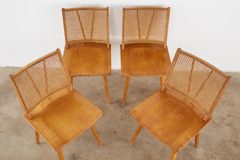 Mid-Century Modern set of four maple dining chairs attributed to Paul McCobb. The chairs feature a caned back conjoined to a shaped saddle seat. Supported by round tapered legs with an H shaped stretcher. Iconic profile with good cane from an estate