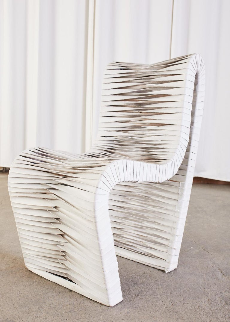 Aesthetic set of four sculptural lounge chairs featuring leather strap supports. The post modern chairs have a unique one piece steel frame that contours your body. Woven leather straps that are dyed white cover the frame with a decorative twist