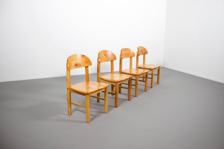 Set of four solid pine wood chairs in very good condition.  Designed by Rainer Daumiller and manufactured by Hirtshals Savvaerk in the 1970s   The chairs have a carved seat and backrest which give them a robust and organic appearance.  The rustic