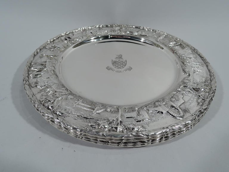 Set of four sterling silver plates with landscape rim. Made by S. Kirk & Son Inc. in Baltimore. Each: Plain well engraved with armorial and Latin motto Mediocria Firma. Wide shoulder with chased and repoussé rural scenes including old stone