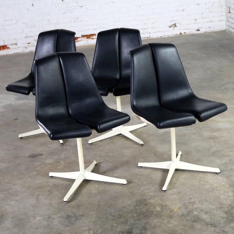Incredible set of four I48 stacking chairs by Richard Schultz for Knoll. This set is in wonderful vintage condition. The black faux leather or Naugahyde is in fabulous shape; however, the white finish on the shells, shaft, and feet has some
