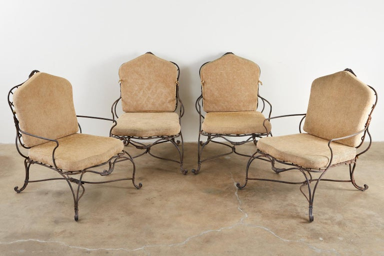 Amazing set of four iron faux bois twig garden lounge chairs by Rose Tarlow Melrose House. Large, substantial frames featuring a delicate faux-bois twig design with ribbon bows. The seat and back have a geometrical lattice inset and the iron has a