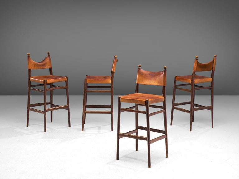 Set of 4 barstools, patinated leather, brass and oak, Scandinavia, 1960s.  Exquisite set of Scandinavian Modern high chairs. The frame is slim and the conical shaped legs are flared positioned from each other. The horizontal slats that connect the