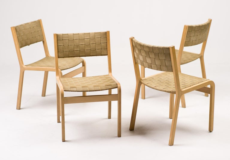 Set of four Danish dining chairs with a beautiful bent beech plywood frame construction similar to the Ax chair designed by Peter Hvidt. Seat and back are upholstered with canvas straps.