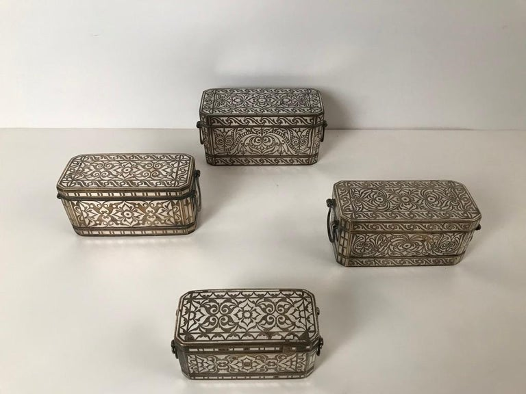 A wonderful collection of four bronze betel nut boxes in various sizes with intricate and quite beautiful inlaid silver designs on all sides. These well made boxes are rectangular with chamfered corners, each with four interior lidded Chambers that