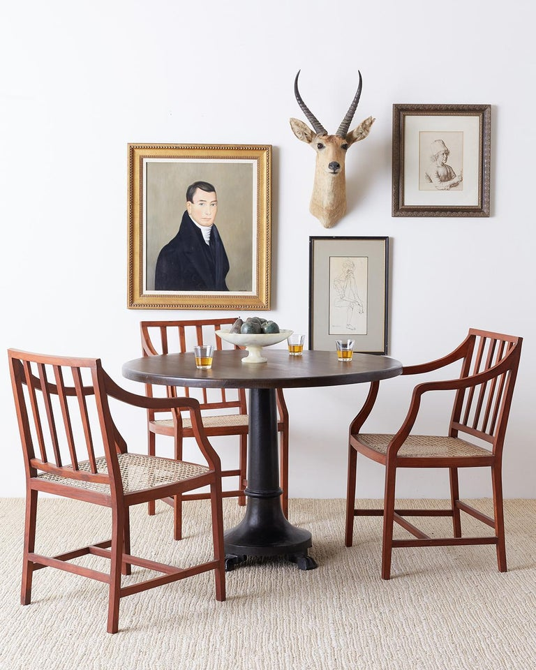 Stylish set of four slat back hand carved dining chairs featuring a hand-caned seat. Each chair has long, graceful finger carved arms and is supported by elegant square legs with H shaped stretchers. Understated with a warm teak finish and excellent
