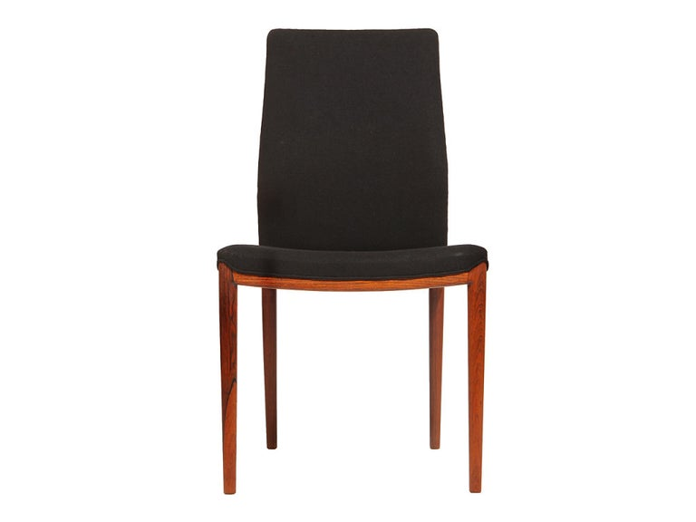 A beautiful set of four Scandinavian Modern dining chairs designed by Helge Vestergaard Jensen. Each chair is rosewood framed and upholstered in black wool. Made in Denmark, circa 1950s. 