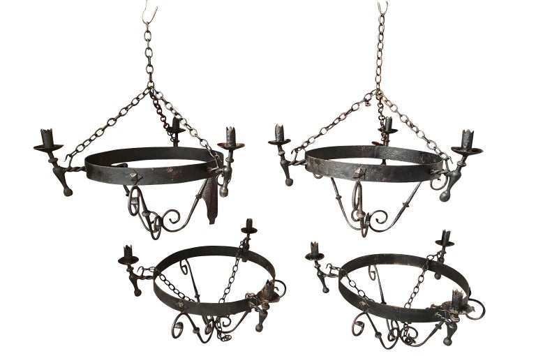 A very handsome set of four chandeliers from Spain. Beautifully constructed from hand forged iron. Stunning statement pieces.